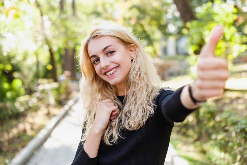Menina fazendo sinal de jóia para câmera