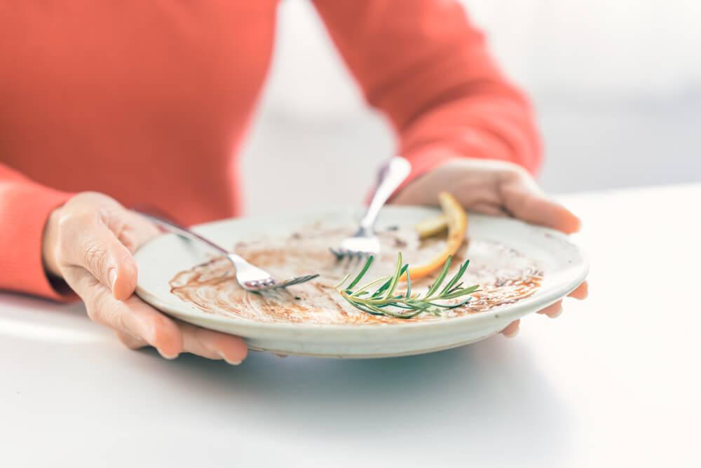 Mãos femininas segurando prato vazio