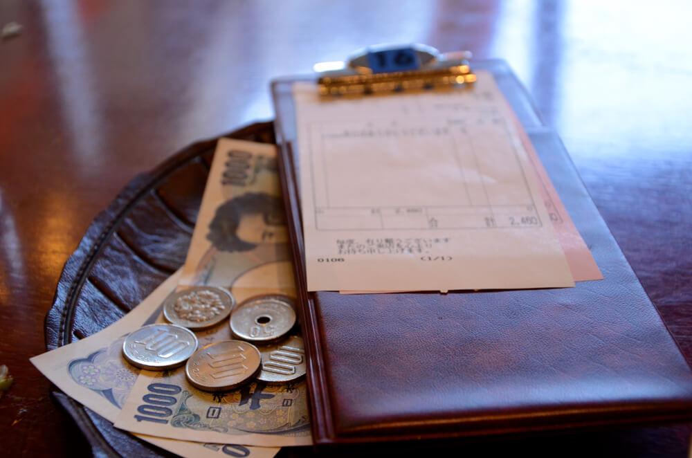 Pote com gorjetas em notas e moedas