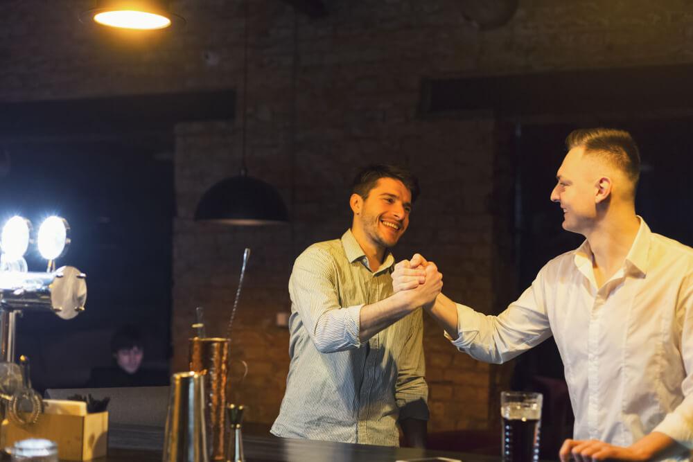 Dois amigos se cumprimentando com um aperto de mãos informal