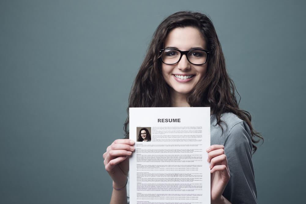 Mulher segurando currículo em inglês sorrindo para a câmera